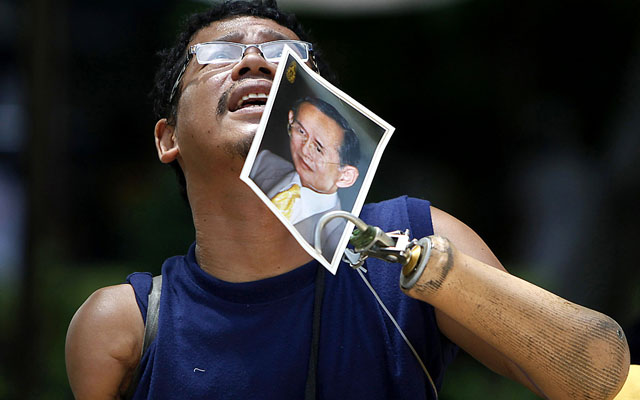 A well-wisher, Supoj Chorkaew, 36, holds a portrait of Thailand's King Bhumibol Adulyadej as he looks up at the building where the king residing, at Siriraj Hospital in Bangkok