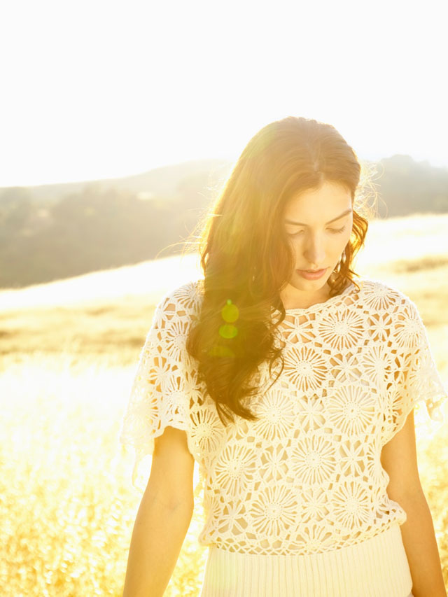 Thoughtful woman walking in nature backlit by the sun with copy space