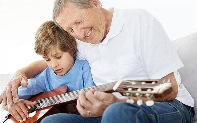 C506T0 Portrait of an old man teaching his grandson how to play the guitar