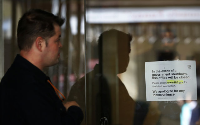 A man views a sign warning that the Internal Revenue Service building is closed at their offices in New York