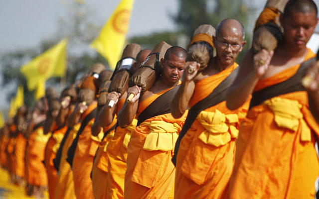 Buddhist monks participate in a procession to mark the anniversary of the enlightenment of Lord Buddha, on the outskirts of Bangkok