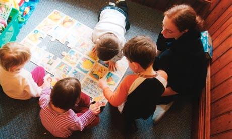 A trainee nursery worker with children in a nursery