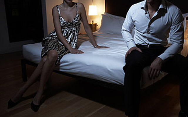 Couple sitting apart on bed, night