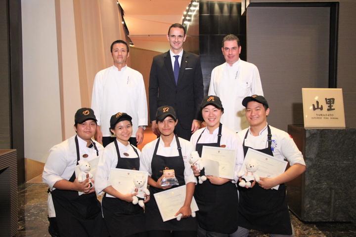 แถวยืน: เชฟ ชิเงรุ ฮางิวาระ (Shigeru Hagiwara) หัวหน้าพ่อครัว (Master Chef) ประจำห้องอาหารยามาซาโตะ, มร. เอ็ดเวิร์ด อี สนุ๊ก (Edward E. Snoeks) ผู้จัดการทั่วไป (General Manager) โรงแรม ดิ โอกุระ เพรสทีจ กรุงเทพฯ, เชฟ แอนโทนี ชอลท์ไมเยอร์ (Antony Scholtmeyer) หัวหน้าพ่อครัวใหญ่ (Executive Chef ) ประจำโรงแรม ดิ โอกุระ เพรสทีจ กรุงเทพฯ แถวล่าง: นางสาวสามิณี สุขจันทร์, นางสาวอรทัย กิตติสิทโธ, นางสาวพิชชากร รามบุตร, นางสาวพิมพ์ลภัส ตันติศรีสุข, นายธาดา เอกประทุมชัย
